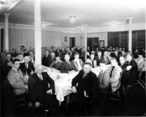 Louie immediately to the right of front post, partially obscured. Louis to the left of the post, second in dark suit. 1946 Football banquet. Photo by King Studio, Jamestown ND